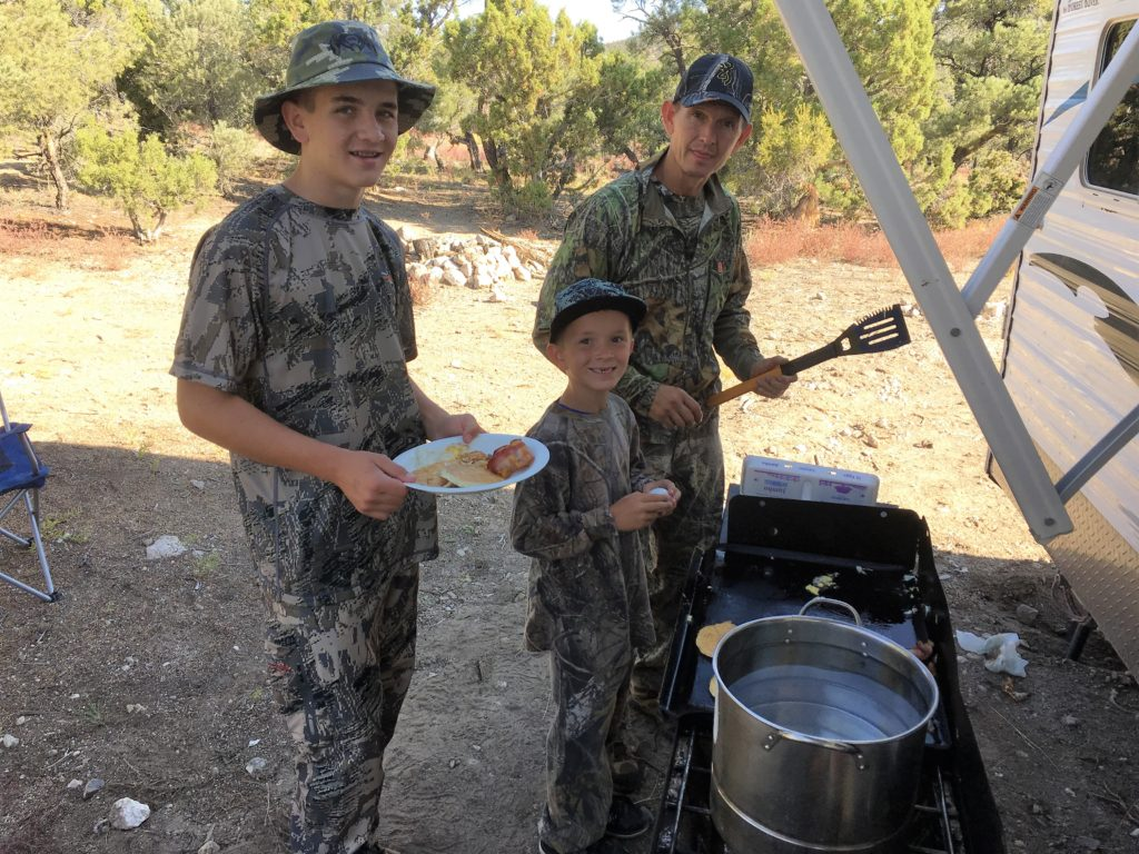 Sons enjoy breakfast at camp